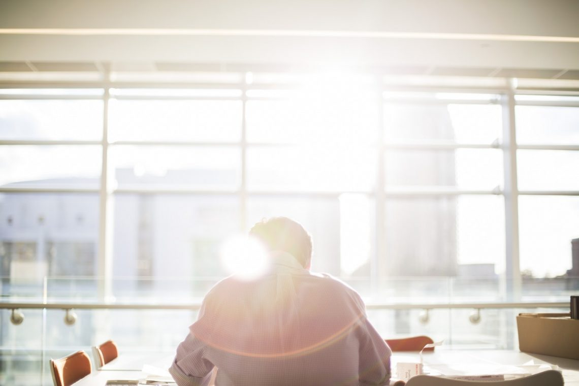 Man in office with sun rising